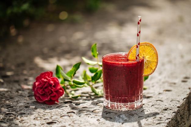 Frullato ai frutti rossi in un bicchiere con una cannuccia su una pietra con fiore