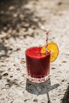 Frullato ai frutti rossi in un bicchiere con una cannuccia su una pietra