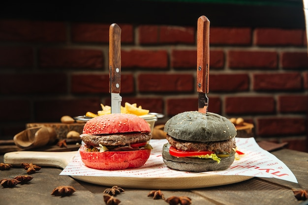 Hamburger di panino rosso e nero con coltelli sul tavolo di legno