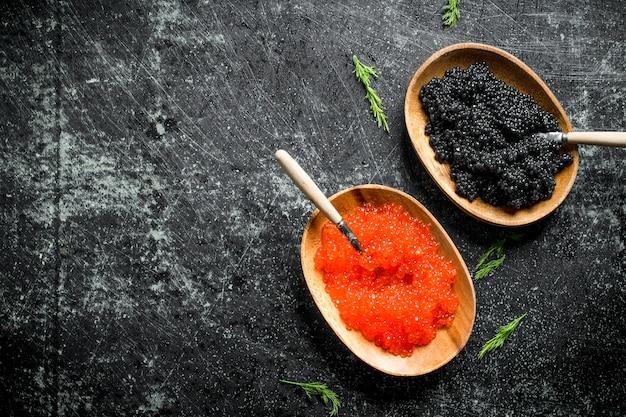 Caviale rosso e nero in ciotole con cucchiai e aneto. su sfondo nero rustico