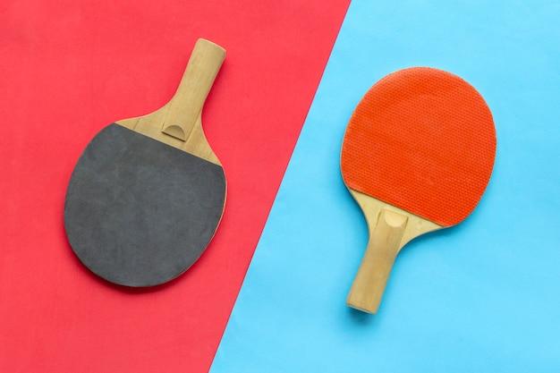 Racchette rosse e nere per ping pong su sfondo blu e rosso.