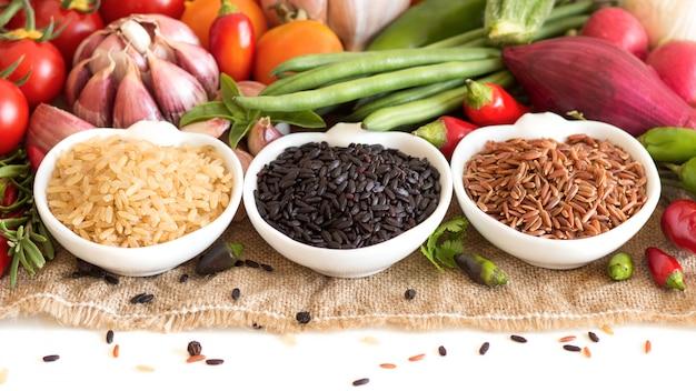Il riso organico rosso, nero e non lucidato in ciotole con le verdure crude si chiude su isolato su bianco con lo spazio della copia