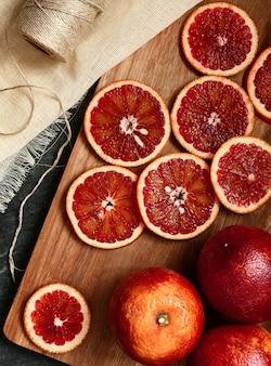 Fetta di arancia rossa su una tavola di legno, vista dall'alto