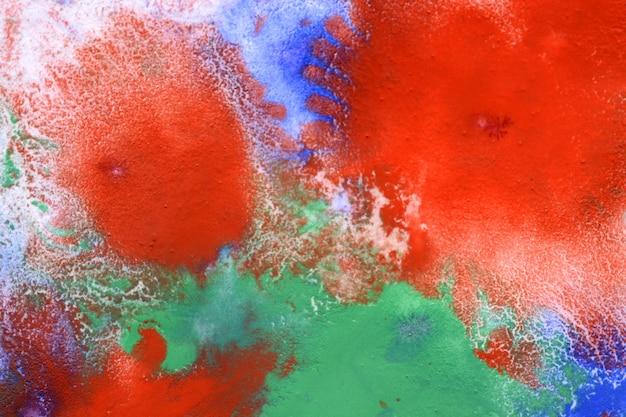 Rosso blu verde diffonde macchie sulla superficie bianca