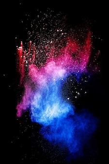 Nuvola di esplosione di polvere blu rossa su sfondo nero. spruzzata di particelle di polvere blu lanciata.