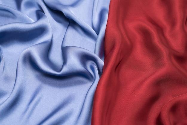 Trama di tessuto di lusso in seta o raso rosso e blu. vista dall'alto.