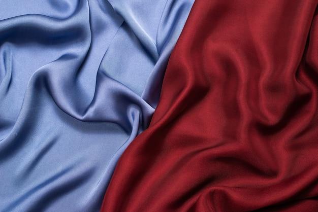 Trama di tessuto di seta o raso di lusso rosso e blu. vista dall'alto.