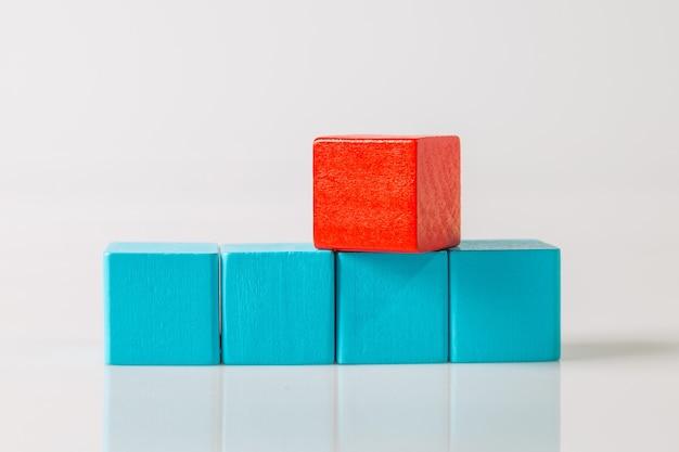 Cubo di forme geometriche in legno rosso e blu isolato su sfondo bianco