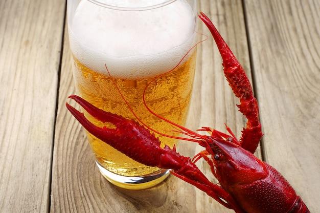 Gamberi rossi bolliti e un bicchiere di birra su un tavolo di legno