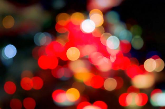 Luce rossa del bokeh dall'automobile sulla strada nella città alla notte. defocused del traffico notturno.