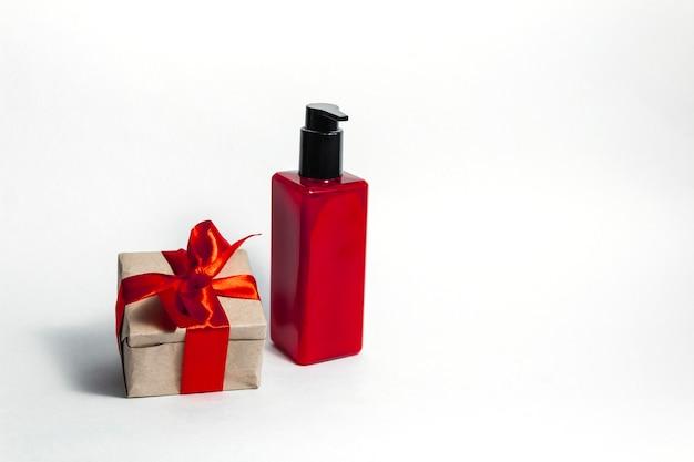 Una bottiglia rossa di lozione accanto a una confezione regalo legata con un nastro rosso