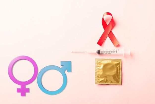 Simbolo del nastro rosso dell'arco preservativo e siringa per la consapevolezza del cancro dell'hiv aids con segni di genere femminile maschile