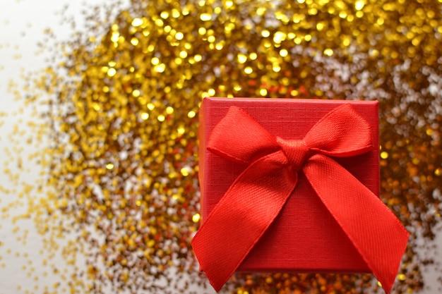 Scatola rossa sullo sfondo scintillante glitter giallo oro