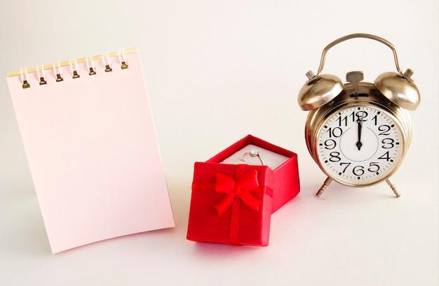 Scatola rossa di regali speciali con un anello e un orologio su una superficie chiara con un posto per un'iscrizione