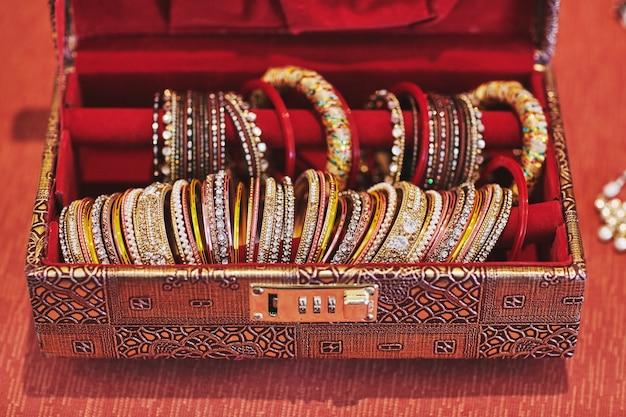 Una scatola rossa con collezione di braccialetti o bracciale glitter per la sposa indiana