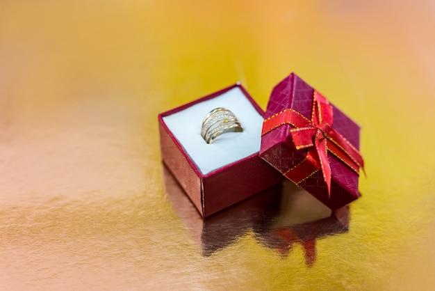 Scatola rossa con anello su sfondo dorato