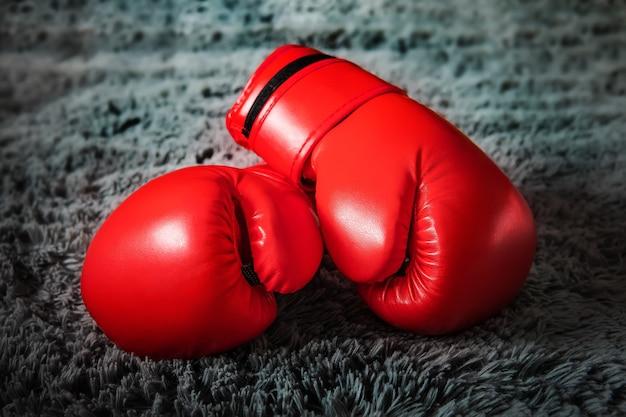 Guantoni da boxe rossi giacciono sul pavimento su un tappeto grigio su sfondo scuro