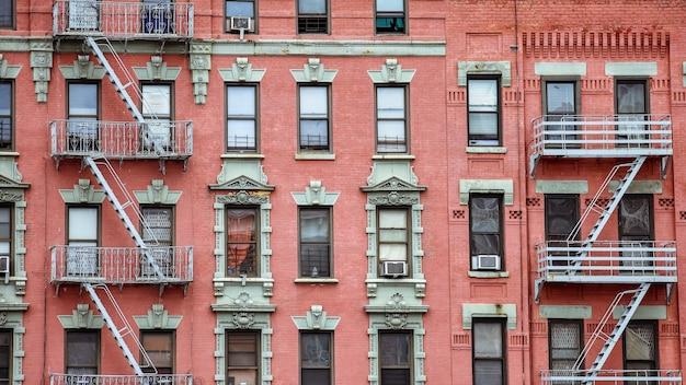 Facciata in mattoni rossi e scale antincendio. harlem, new york.