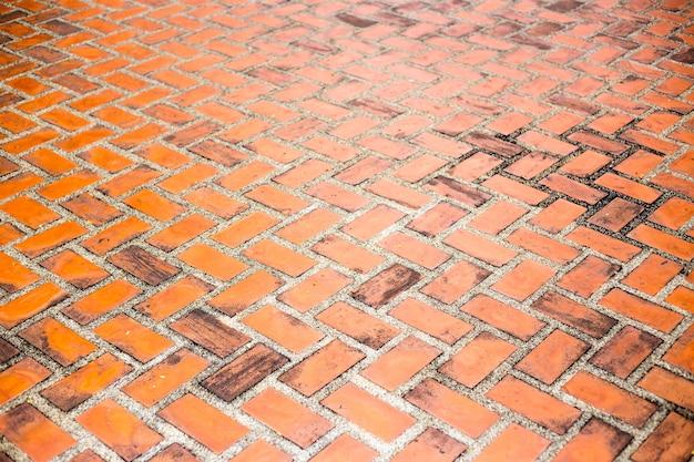 Struttura del reticolo del pavimento in mattoni rossi per lo sfondo