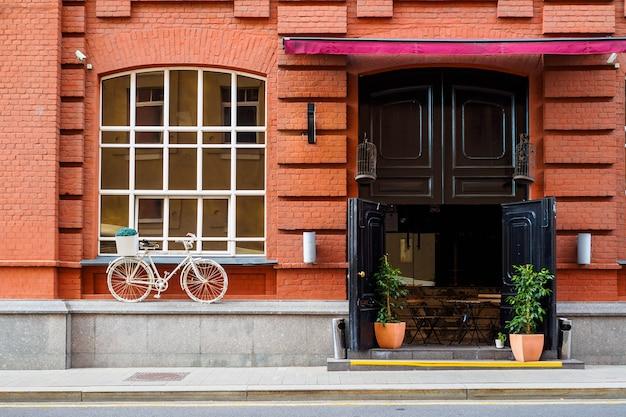 Facciata di una casa in mattoni rossi con finestra e porta e bicicletta vintage bianca Foto Premium