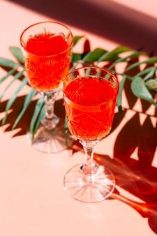 Cocktail rossi luminosi su sfondo colorato con foglie