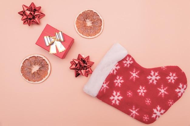 I regali rossi e marroni cadono negli stivali di babbo natale o di san nicola sul rosa