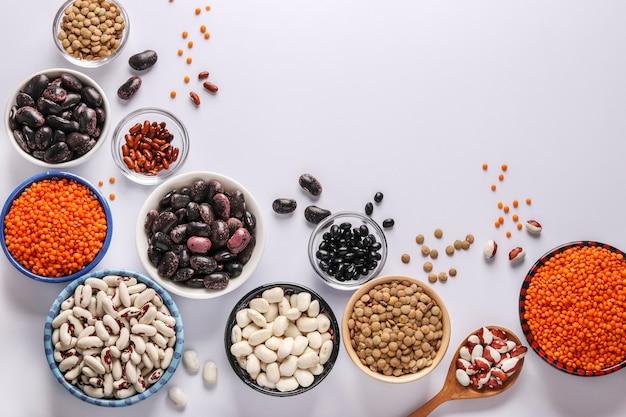 Lenticchie rosse e marroni, fagioli neri, marroni e bianchi sono legumi che contengono molte proteine si trovano in ciotole su sfondo bianco, il concetto è mangiare sano, vista dall'alto