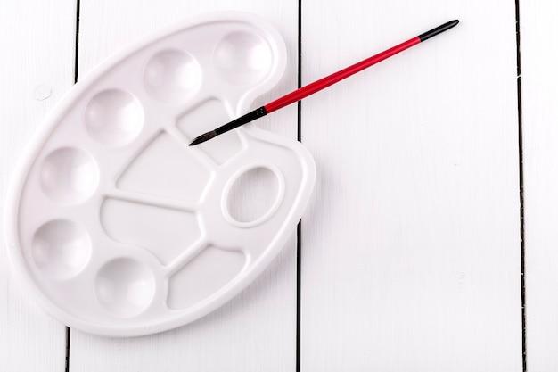 Pennello rosso per disegnare e nuova tavolozza vuota su tavolo in legno bianco