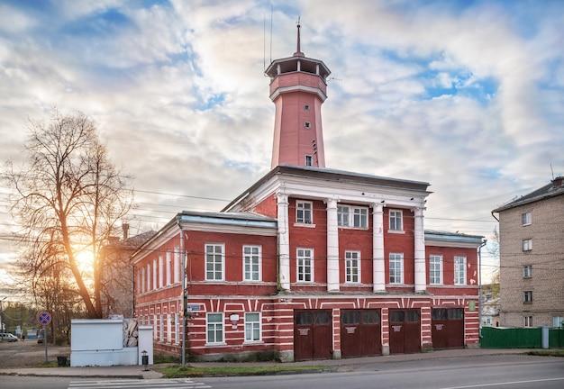 Edificio rosso di una torre antincendio a uglich con un'alta torre sotto i raggi del sole autunnale