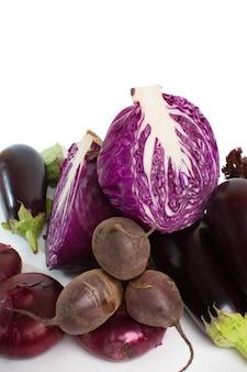 Il cavolo rosso è un primo piano trasversale, della melanzana, della cipolla rossa, della barbabietola e dell'insalata su bianco