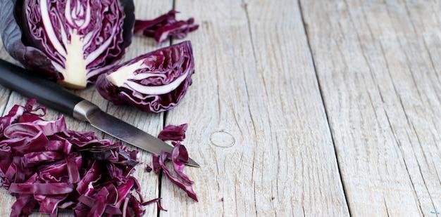Cavolo rosso con un coltello su un tavolo di legno