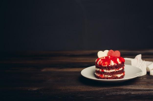 I dolci rossi della torta deliziano il dessert nel fondo di legno dei piatti