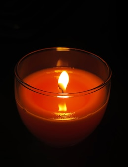 Candela rossa in candeliere di vetro trasparente che brucia nell'oscurità