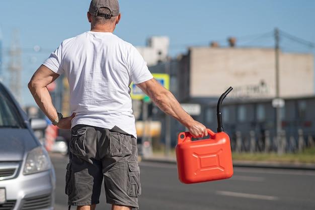 Una bomboletta rossa sull'asfalto vicino alla macchina. l'auto è rimasta senza benzina e si è fermata. un giovane che spera in aiuto sulla strada da altri conducenti.