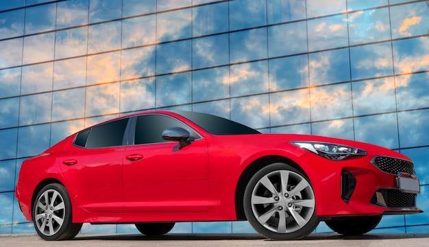 Automobile rossa su una priorità bassa del cielo blu con le nubi bianche.
