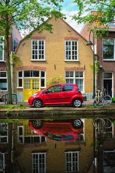 Automobile rossa sull'argine del canale in via di delft paesi bassi delft