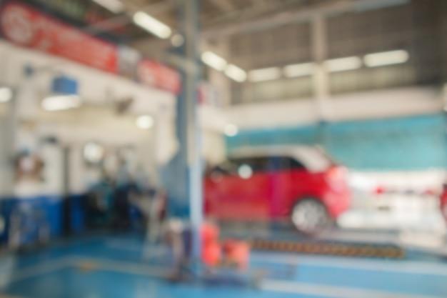 Ascensore rosso per auto alla stazione di manutenzione nel centro di servizio automobilistico sfocatura sfondo astratto