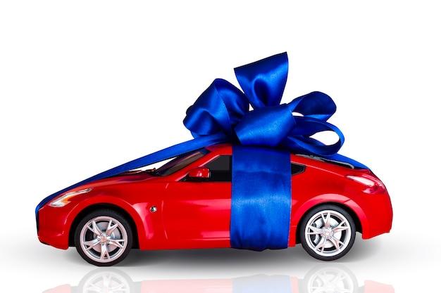 Automobile rossa con fiocco blu come regalo isolato su sfondo bianco.