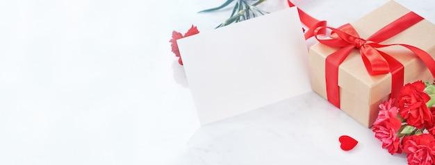 Bouquet di fiori di garofano rosso con regalo kraft avvolto legato con nastro isolato sul tavolo di marmo bianco, si chiuda.