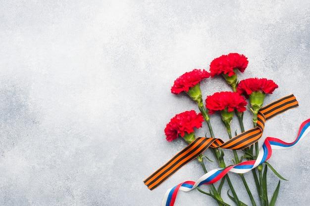 Garofani rossi e nastro di san giorgio su uno sfondo concreto.