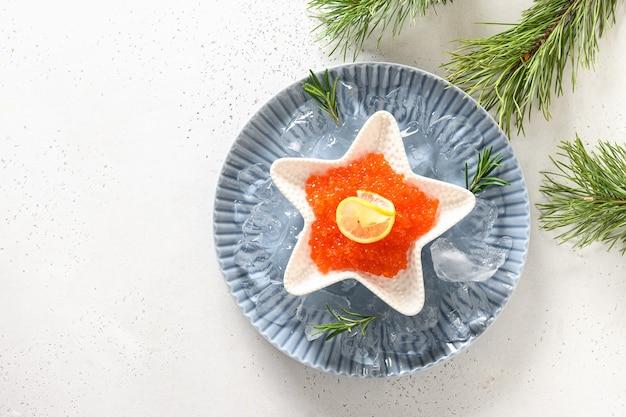 Caviale rosso in una ciotola a forma di stella servito con cubetti di ghiaccio per la festa di natale sul tavolo bianco. vista dall'alto. spazio per il testo.