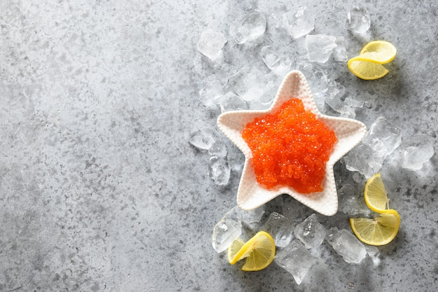 Caviale rosso in una ciotola a forma di stella servito con limone e cubetti di ghiaccio per la festa festiva sul tavolo di pietra grigia. vista dall'alto. spazio per il testo.