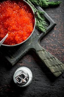 Caviale rosso in una ciotola con cucchiaio, aneto e sale. su rustico