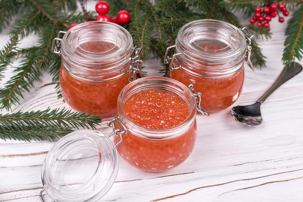 Caviale rosso in un barattolo di vetro su fondo di legno bianco invecchiato. piatto principale capodanno.