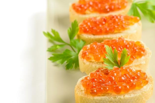 Caviale rosso sulle fette di pagnotta bianca fresca con prezzemolo sul piatto bianco.