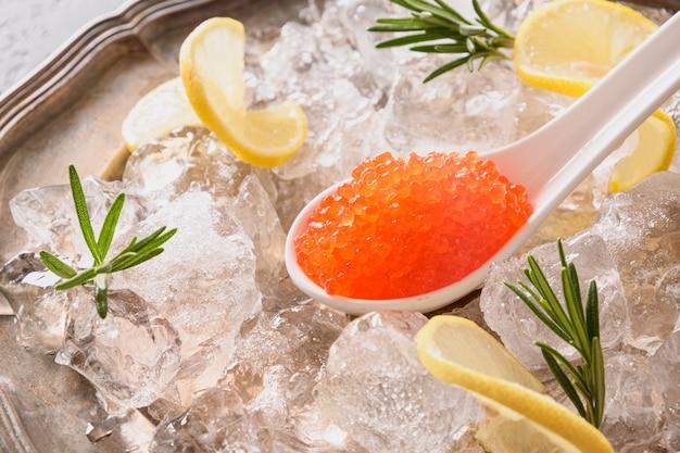 Il caviale rosso nel cucchiaio guarnisce il limone sul cubetto di ghiaccio. avvicinamento.