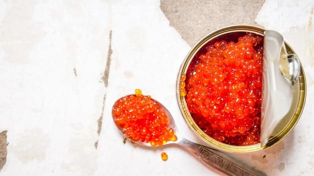 Caviale rosso in barattolo di latta e cucchiaio. sulla tavola rustica. spazio libero per il testo. vista dall'alto