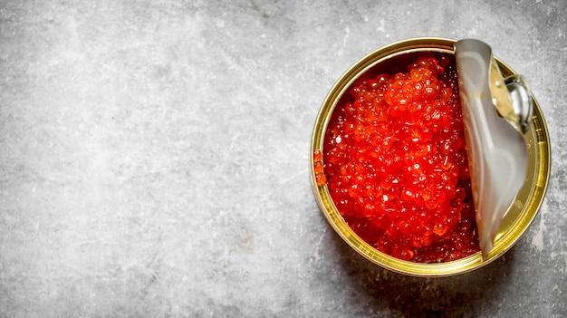 Caviale rosso in barattolo di latta. sul tavolo di pietra. spazio libero per il testo. vista dall'alto