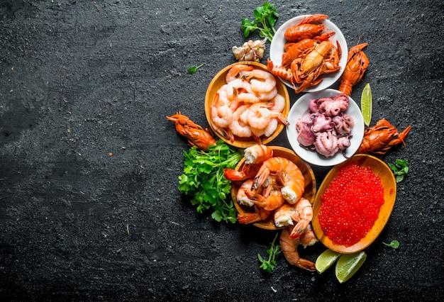 Caviale rosso con frutti di mare, prezzemolo e fettine di lime.