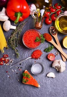Caviale rosso con spezie e verdure e più cibo in giro su sfondo nero con texture